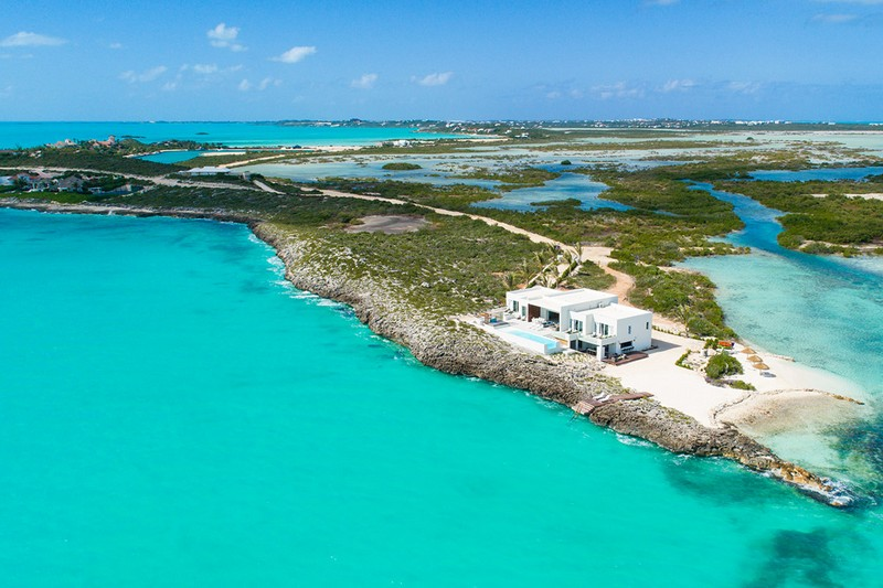 Tip of the Tail, one of our luxury Turks and Caicos Villas, sits at the end of a sandy peninsula. The view is from the air and the landscape, a lush green and blue, reaches into the distance.