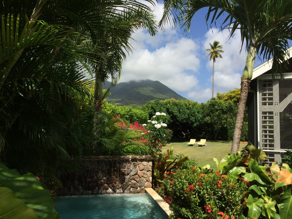 The mist covered peak of Mount Nevis looms in the distance forming a majestic backdrop to the garden at Summerside; on of our luxury villas in Nevis