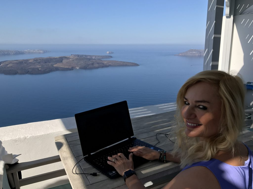 Alexandra sits happily at her computer on the balcony of Gaia, one of our favourite Santorini villas.