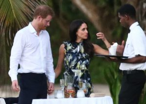 Meghan Markle holding hands with Prince Harry while discussing something with a waiter