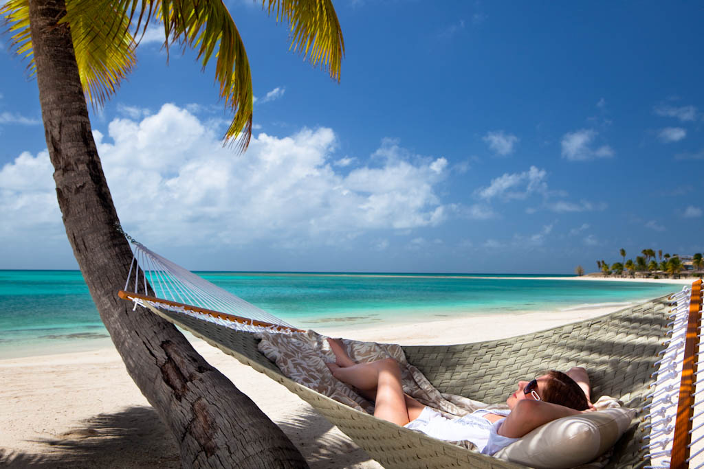 Lady reclining in a hammock on the beach at a Luxury Caribbean Resort