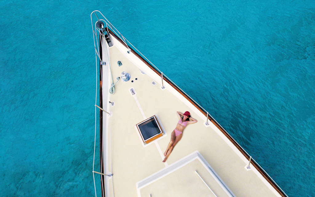 A girl sunbathes on the deck of a boat on a deep blue sea