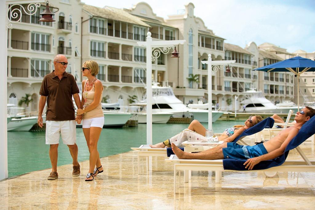 An elderly couple walk past sun-bather at the Marina in Port Ferdinand Resort