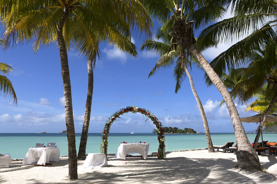 Floral arch over looking clear blue waters cooly shaded by palm trees on a white sand beach