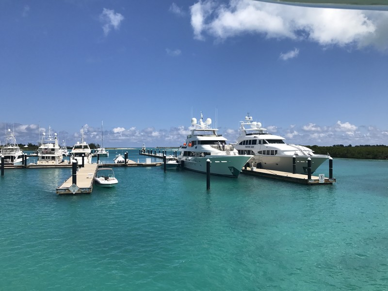 A number of sleek white yachts and smaller skiffs berthed at the Blue Haven Marina