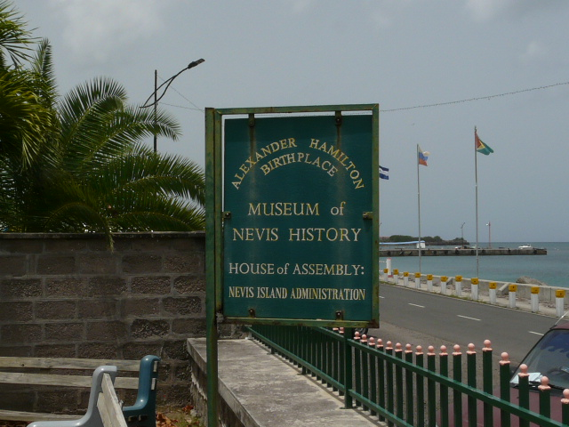 Dark green, metallic sign post of the museum of Nevis history looks a bout as old as the history it provides
