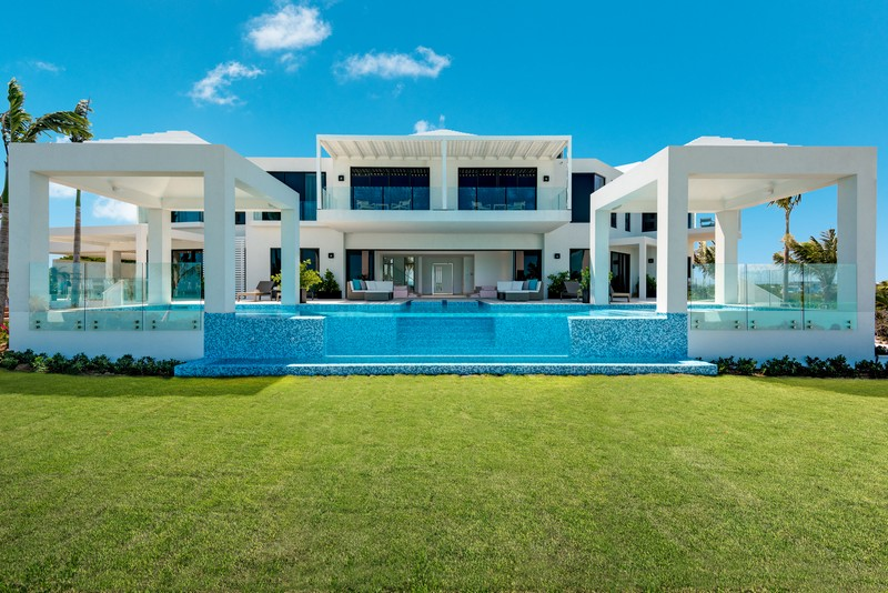 The clean-cut, almost cubist, white lines of Triton Villa in Turks and Caicos as seen across the lush green lawn. Before the villa, two white pagodas sit at either end of the infinity pool. The pool itself has a thick glass front and the stairs leading out of the pool and up to the sun deck can be seen.