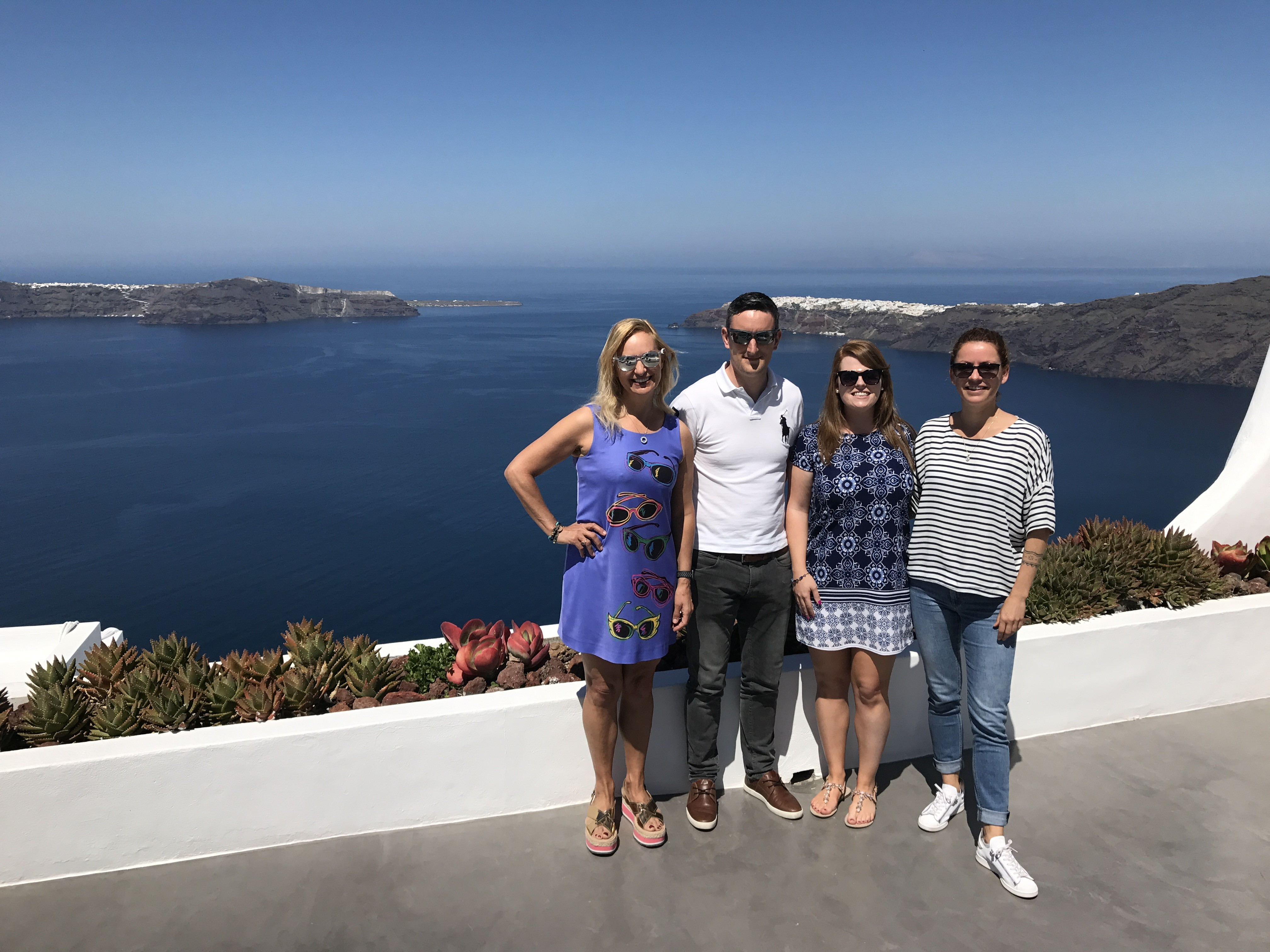 Alexandra, Linda, Sean, and a villa manager pose for a photo in front of the astonishingly pretty view from Erossea Villa