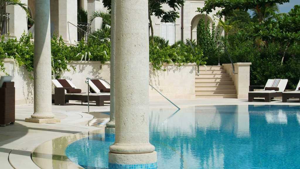 Marble pillars thrust gracefully from the intensely blue water of the swimming pool at One Sandy Lane
