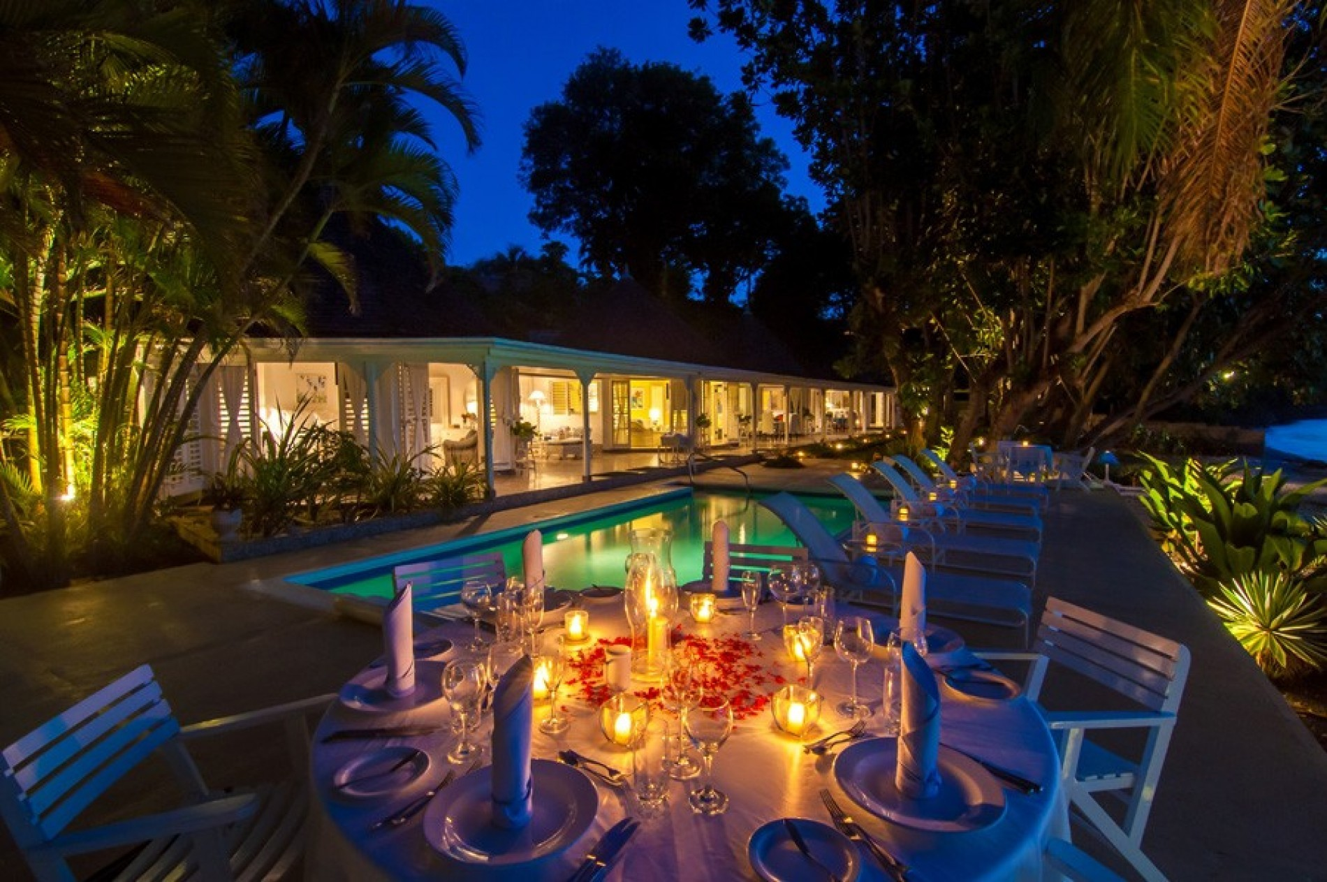 The pool area glows seductively in the Jamaican night. A prettily set dinner table scattered with rose petals and candles warms the images foreground.