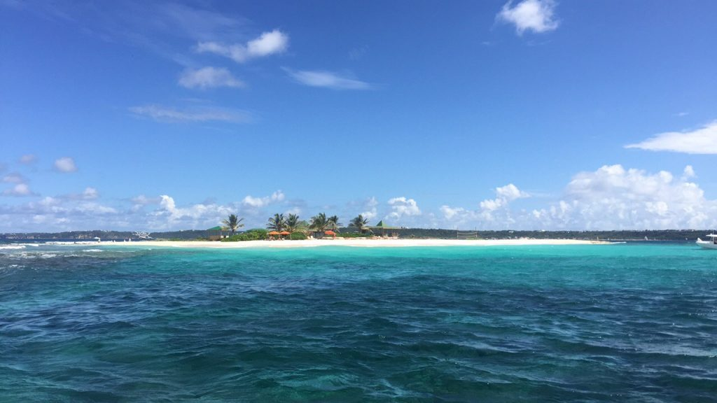 A white strip of beach, palm trees, and beach bars on Sandy Island in Anguilla seen from the sea