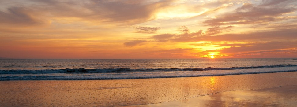 The sun dips towards the horizon behind a wide, peaceful beach at Punta Mita
