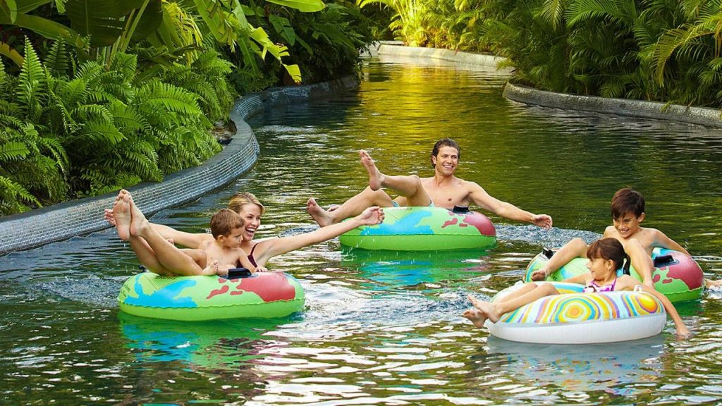 A family on inflatable rings floats down the Lazy River at the Four Seasons Resort at Punta Mita