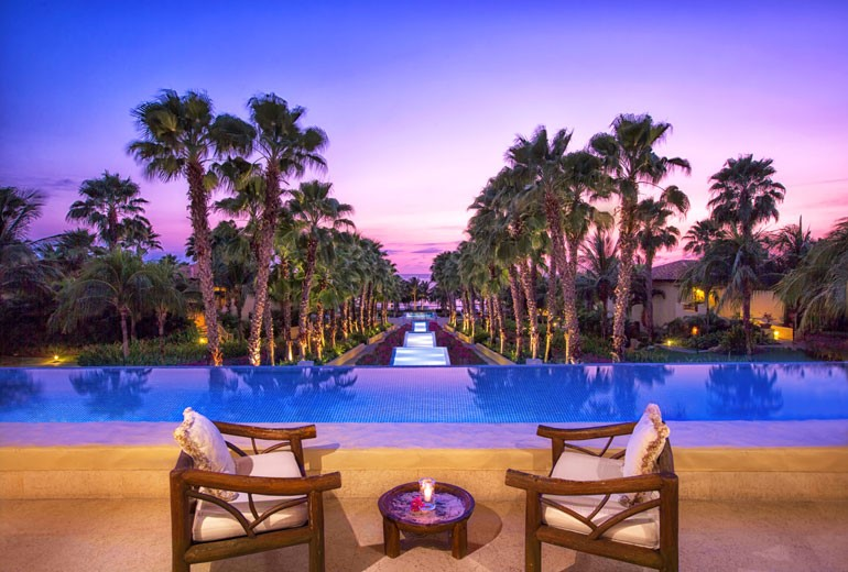 View down an avenue of lush palm trees at the St Regis Resort in Punta Mita