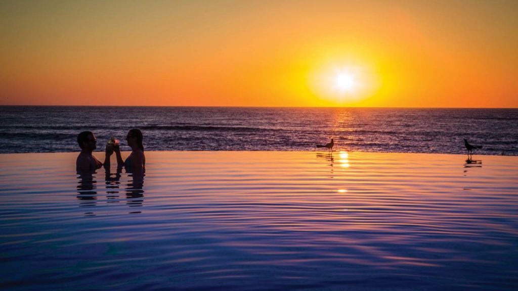 A couple in an infinity pool silhouetted against the setting sun at Punta Mita