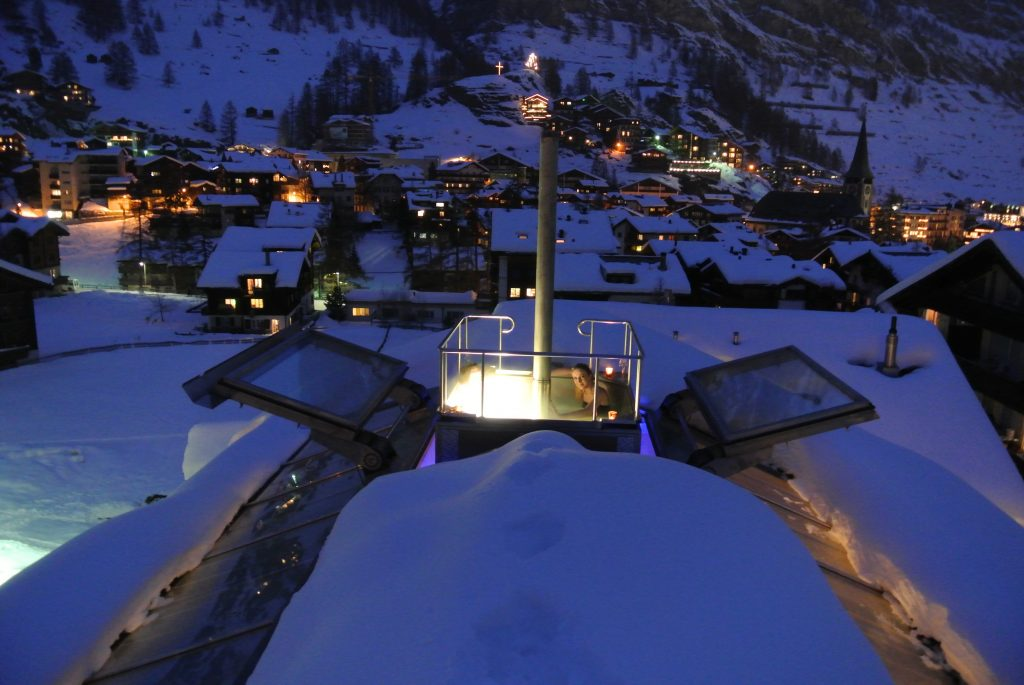 A loan bather sits in the warm, bubbly comfort of the rooftop Jacuzzi of the Backstage Chalet in Zermatt