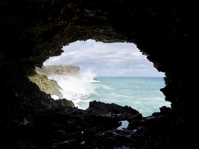 The sea crashes against the rocks outside animal flower cave in barbados
