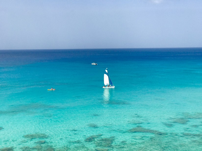 A sailing boat and kayak manoeuvre gracefully through the clear blue waters of the West coast of Barbados