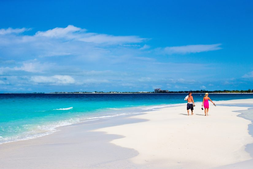 A couple walk across the white sand at Grace Bay beach