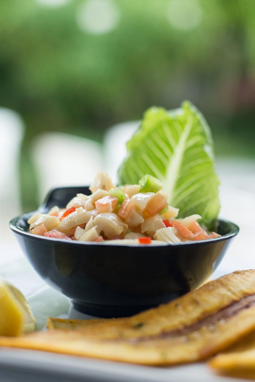 Conch Salad in a black bowl served with plantain