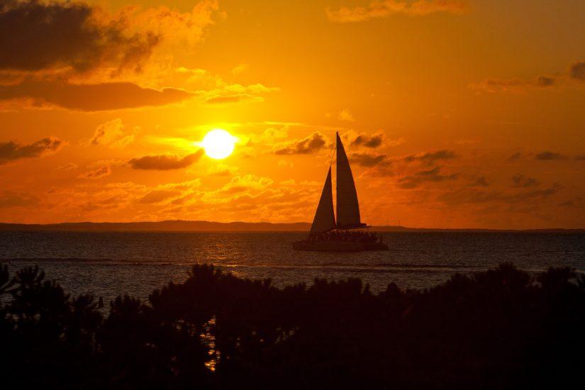 A catamaran sails gracefully through the evening sun at Turks and Caicos