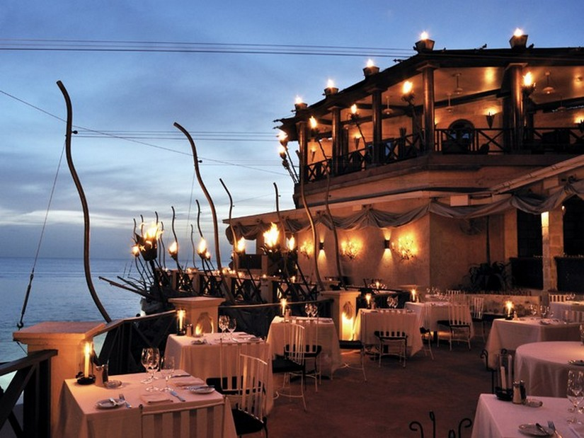 The outside dining area at the cliff restaurant in Barbados overlooking the sea and gently lit by candles