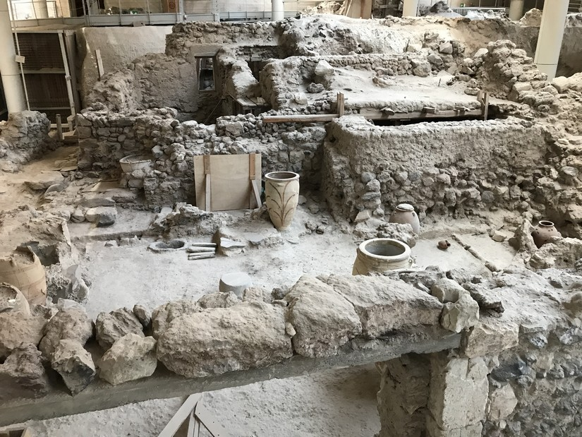 The archaeological excavation at Akrotiri shows the remains of houses, clay pots, and streets. Everything is a pale shade of grey