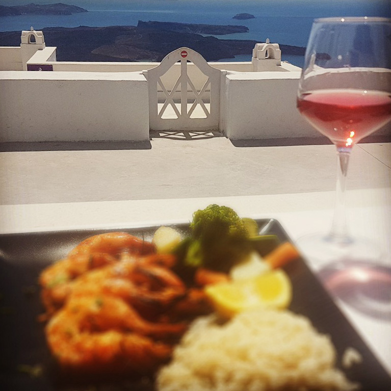 Closeup of a delicious plate of Greek seafood framed by the blue sea on the horizon