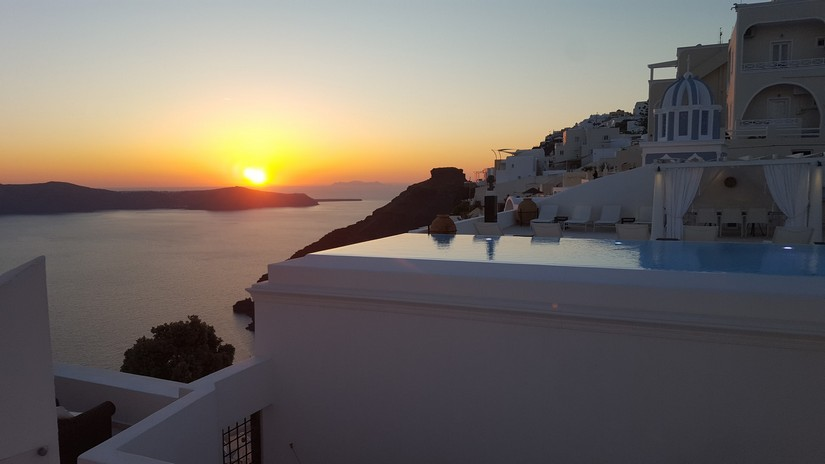 The sun setting in the distance behind the beautiful white village in Oia
