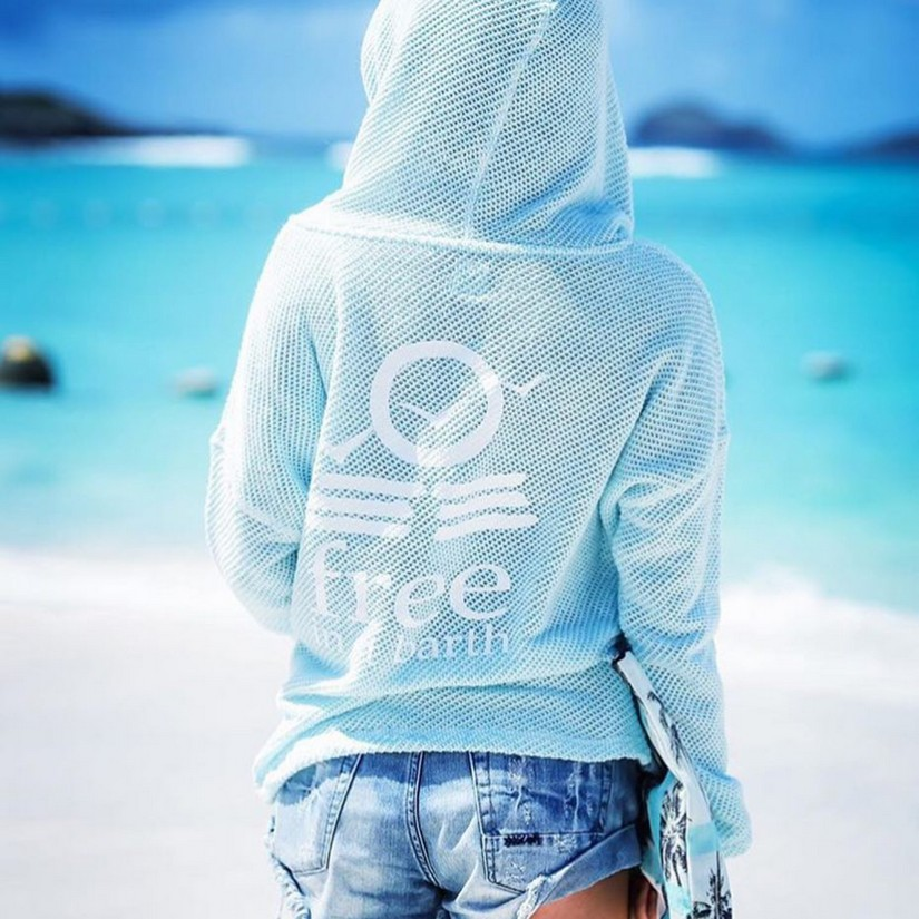 A girl in a blue hoodie from behind looking at a beach