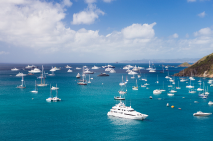Many luxury yachts floating serenely in a bay on the calm blue water around St Barths