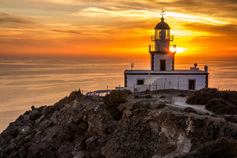 The Akrotiri Lighthouse watches the sun setting into the sea in an epic display of golden loveliness