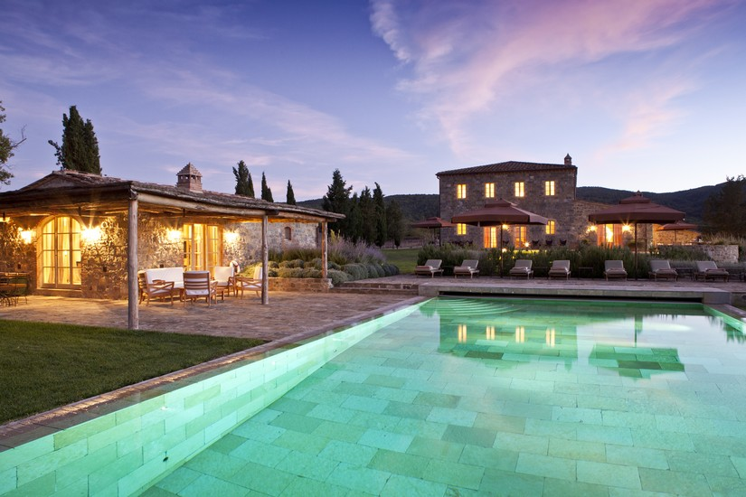 A huge swimming pool before a large country house style villa in Italy