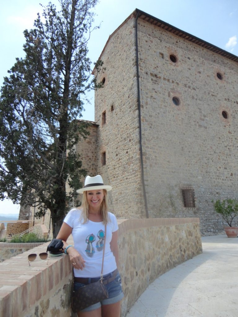 Alex standing in front of a classically designed building in Tuscany