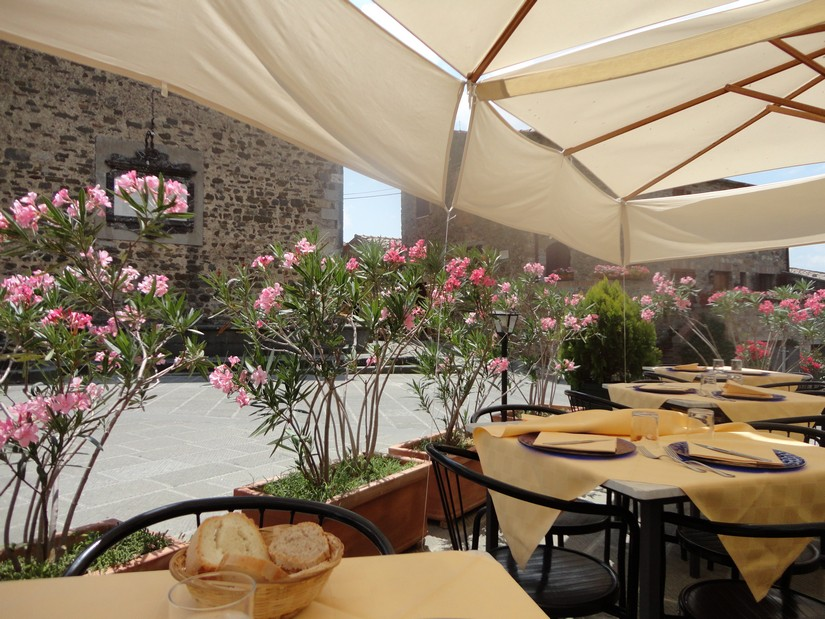 Pretty flowers underneath a parasol in a restaurant at an Italian Piazza