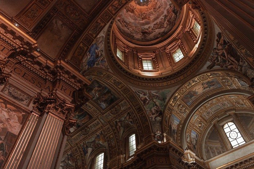 A stunning painted ceiling and ornate architecture in a cathedral in Rome