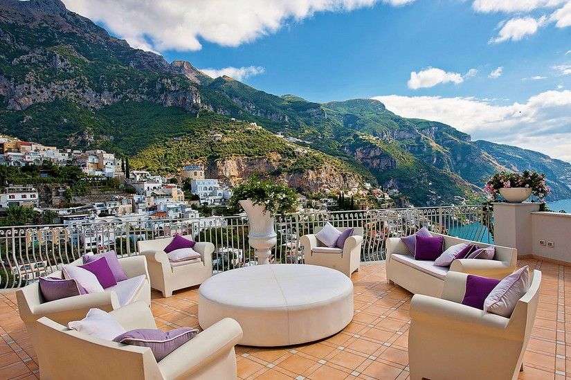 Purple cushioned cream furniture rests tastefully on the balcony area at Gulia Villa in the Amalfi Coast.