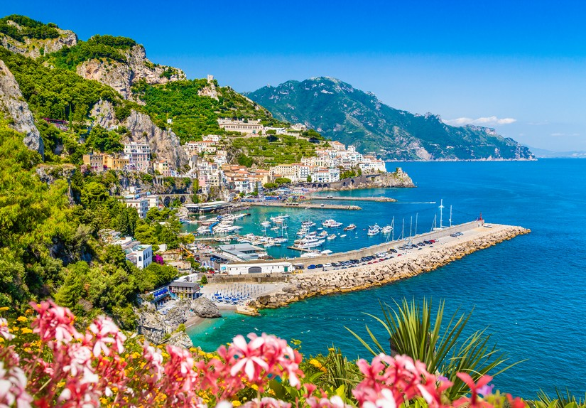 Pretty buildings creep up the side of an astonishingly green hillside. Below the entrancing blue water of the sea is bisected by a long pier that protects a harbour full of shining white boats and yachts. This is the Amalfi coast at it's prettiest