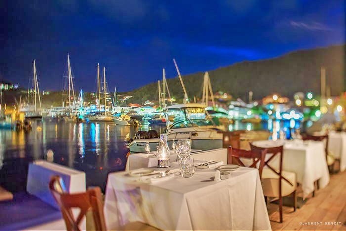 Pier-side table at Bagatelle Restaurant in St Barts over-looking a forest of masts and yachts twinkling prettily in the gently falling dusk