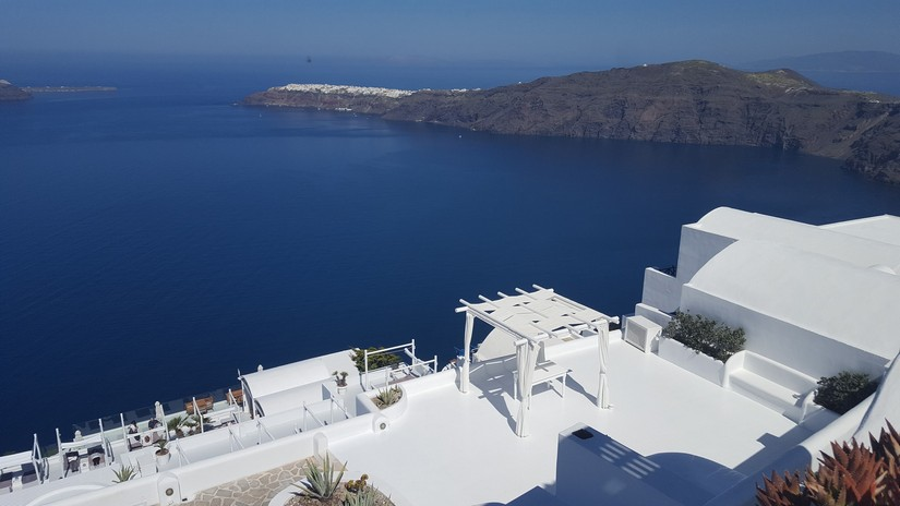 A view of Oia from an elevated position above one of the villas in Santorini. The image is a study in crisp white and deep blue.