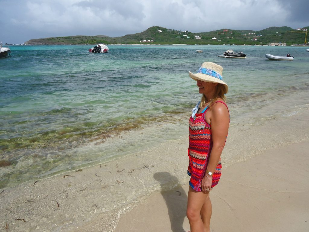 Alexandra in a fetching straw hat staring poignantly out to see at Guanahani; one of the top restaurants in st barths.