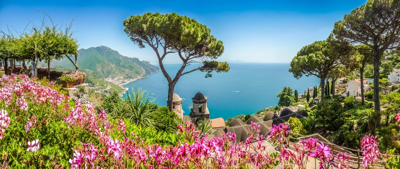 The Mediterranean sub blazes down merrily on a hillside landscape on the Amalfi coast marked by beautiful trees, intriguingly shaped terracotta-roofed building and striking pink flowers
