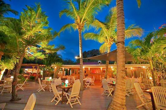 Jauntily lit palm trees push through the smooth polished decking and tower splendidly over the dining area at L'Espirit; considered to be one of the best places to eat in St Barts