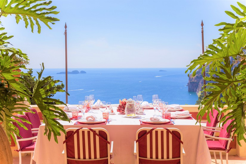 Lunch is set at a peach coloured table overlooking the amalfi coast
