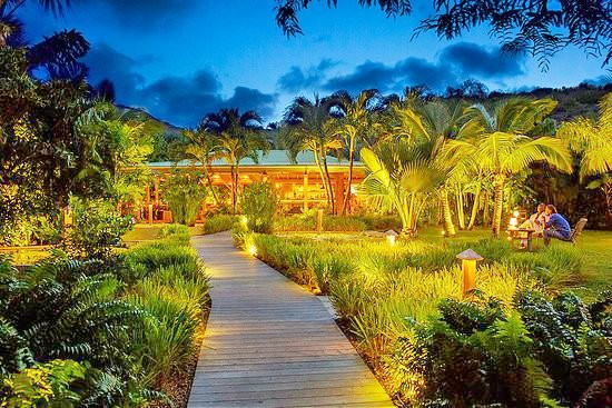 A path of wooden decking leads through the gently lit palm trees and lush foliage to Tamarin restaurant. The restaurant itself looks warm and welcoming with wooden walls and fixtures.