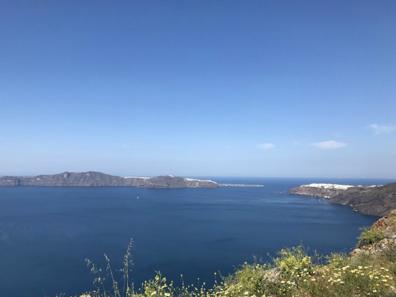 The small white-washed town of Oia in the distance. Sea in the foreground.