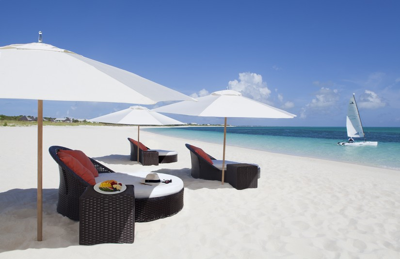 Massively comfortable wicker beach loungers shaded by parasols on grace Bay beach on Providenciales. One of the things to do in Providenciales is absolutely nothing!