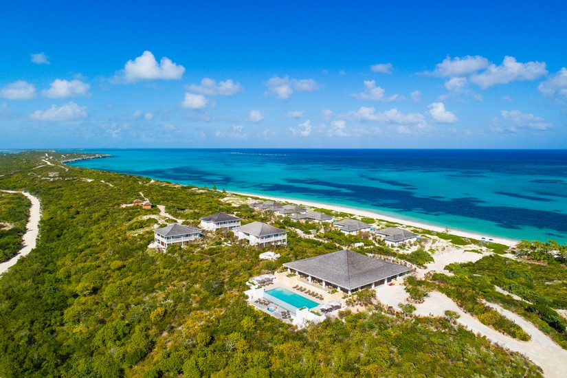 Sailrock resort peeks out from the lush tropical trees along the sandy shore on Sout Caicos