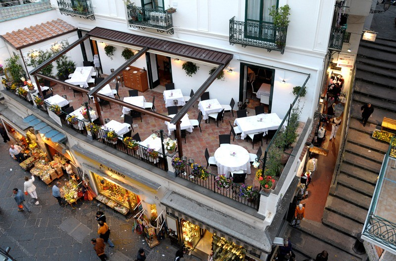 Aerial shot of the outdoor dining area at Da Gemma which is secluded from the busy street outside. One of the best amalfi coast restaurants.