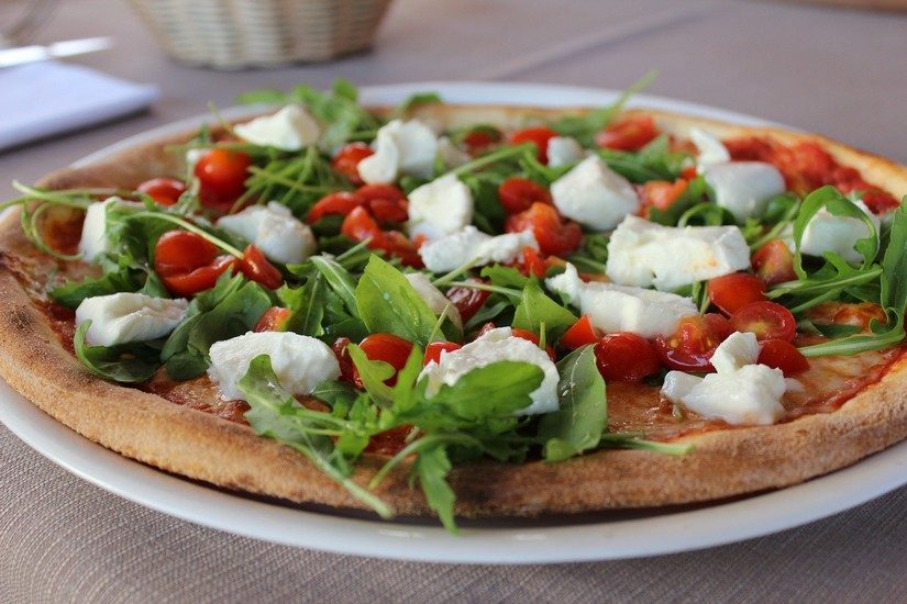 a delicious pizza with fresh mozzeralla, tomatoes and basil